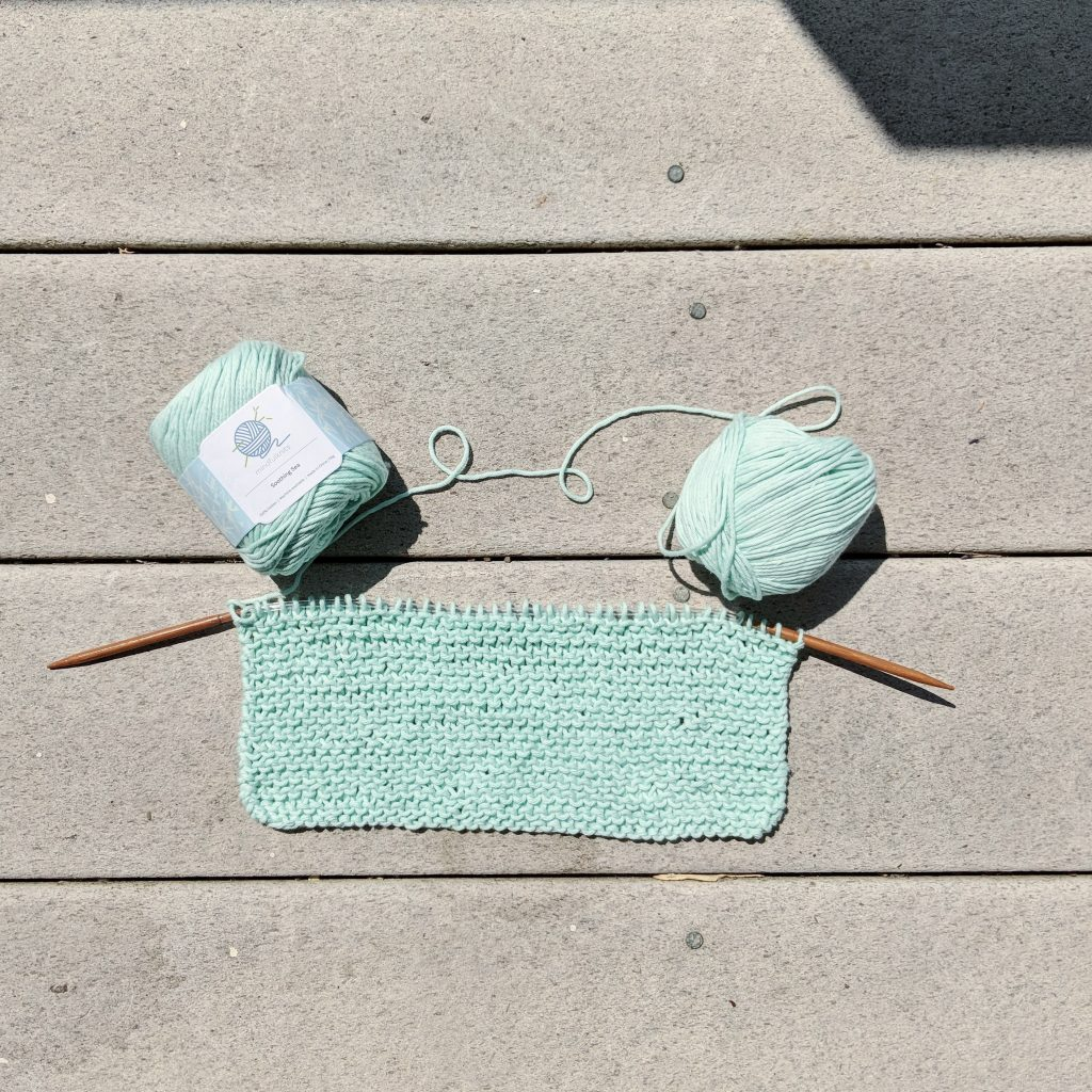 A have completed yarn washcloth project in Mindfulknits' Soothing Sea color is displayed on a surface.