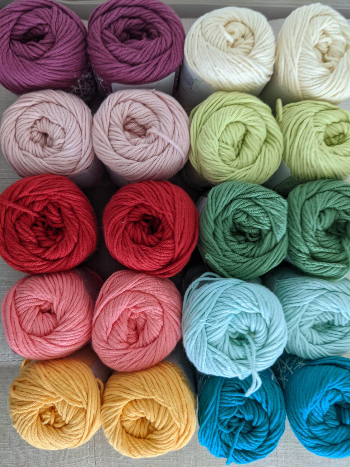 A picture with the 10 colors of mindfulknits yarn from the Zen, Tropical, and Flora bundles.